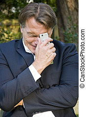 unhappy businessman cluching his cellphone with desperation.