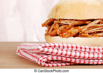 macro pulled pork sandwich on checkered napkin