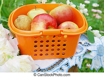 iRed apples in the orange basket, rural still-life