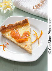 A piece of citrus tart with orange zest bird - A slice of...