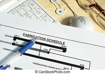 Fabrication schedule with computer monitor and manila...