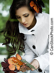Beautiful brunette collecting leafs