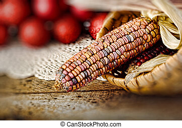 Ear of Indian corn in basket with Christmas balls in background