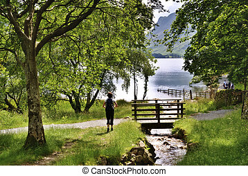 Hiking beside Buttermere - A female hiker approaching a...
