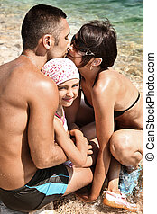 Young family embracing on a sandy beach