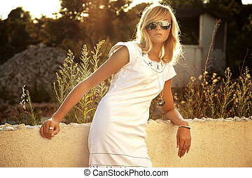 Portrait of the beautiful blond girl in sunglasses