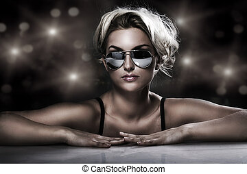 studio shot of young blonde wearing stylish sunglasses