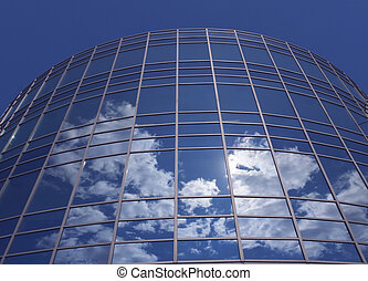 Windows of skyscraper with reflections against blue sky