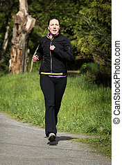 female jogger - women in sportswear jogging in a park