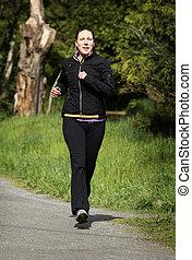 female jogger - women in sportswear jogging in a park