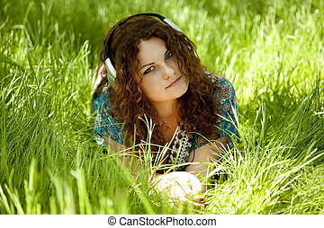 Redhead girl with headphone at green grass