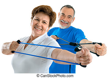 seniors in gym - couple of active seniors doing exercises...