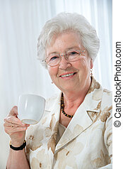 senior woman - beautiful senior woman enjoying a cup of tea...