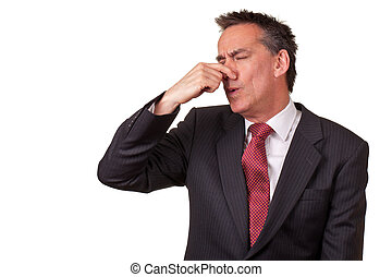 Middle Age Businessman in Suit Smelling Something Bad