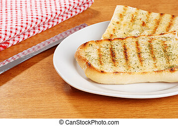 garlic bread with knife - garlic bread on a plate with knife
