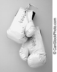Gloves - White boxe gloves pending from a nail on a wall