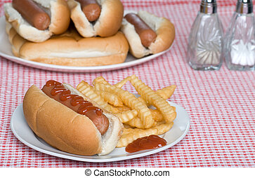 hotdog and french fries on checkered tablecloth
