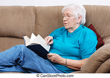 senior woman turning pages of book - portrait senior woman...