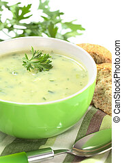Cream of potato with herbs and green onions garnished with parsley and served in a green bowl with bun and parsley (Selective Focus, Focus on the front of the parsley in the soup)