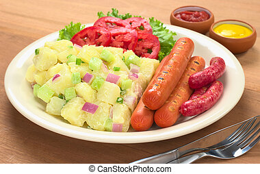 Sausages and potato salad with red and green onions and cucumber with a mayonnaise-cream dressing and tomato slices on plate with ketchup and mustard in the back (Selective Focus, Focus on the front o