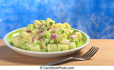 Potato salad with green and red onions and cucumber with a mayonnaise-cream dressing garnished with blue background (Selective Focus, Focus on the front of the salad)