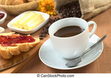 Hot, fresh coffee with croissant with strawberry jam, butter and coffee beans in the back (Selective Focus, Focus on the front rim of the coffee cup)