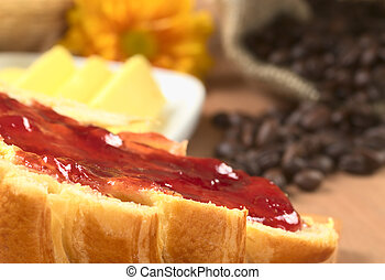 Strawberry jam spread on croissant with butter and coffee beans in the back (Selective Focus, Focus on the front of the spread jam)