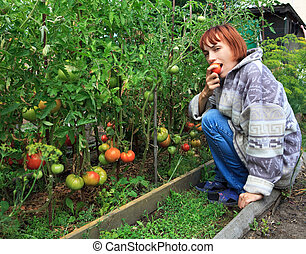 Girl eats ripe tomato.