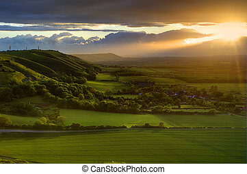 Stunning Summer sunset over countryside escarpment landscape...