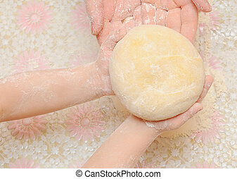 A child is helping mom to knead the dough for baking