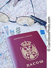 passport, eyeglasses and money on the map