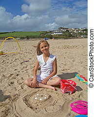 smiling girl playing with sand - on the beach on cornwall uk