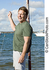 Happy laughing forties man standing in a sailing boat.
