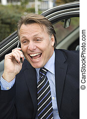 happy businessman on cellphone while sitting in his car