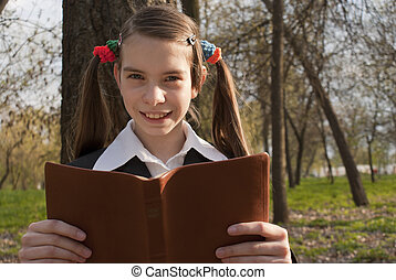 Teen girl with the Bible in a park