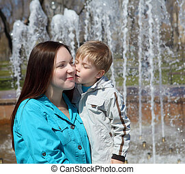 young boy and his mother walks in the park