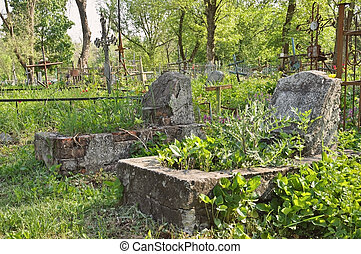 Graveyard: old abandoned graves and rusty crosses -...