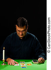 Tarot reader having a concentrated look at a spread of cards