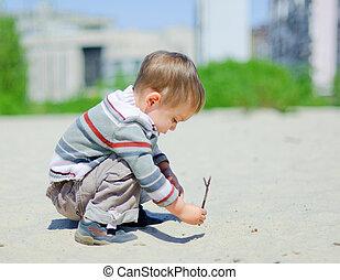 The Boy On Sand - The cute boy plaing on a sand