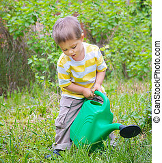 Young Boy In The Garden - Cute little boy watering the...