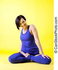 Beauty woman smile in lotos asana - blue on yellow
