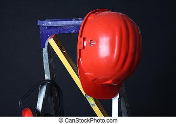 Red helmet on step ladder over black