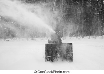 Man Snow Blowing Driveway - A man using a snow blower to...