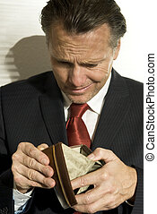 depressed businessman looking into his empty wallet.
