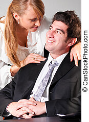 flirting at office - businesswoman is embracing her teammate...
