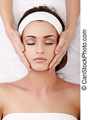 Spa treatment - Beautiful young woman enjoying a facial...