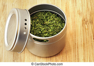 Parsley flakes in aluminum shaker - Food ingredient: dried...