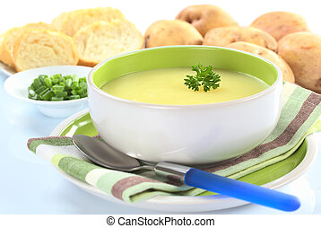 Fresh potato cream soup garnished with a parsley leaf with green onion, baguette slices and raw potatoes in the back on a slightly bluish surface (Selective Focus, Focus on the parsley leaf in the bow