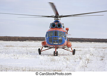 Helicopter in tundra prepares to take off