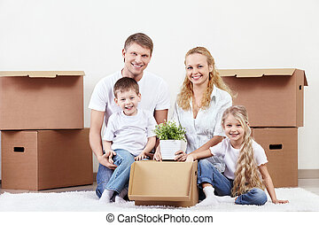 Families with young children unpack boxes